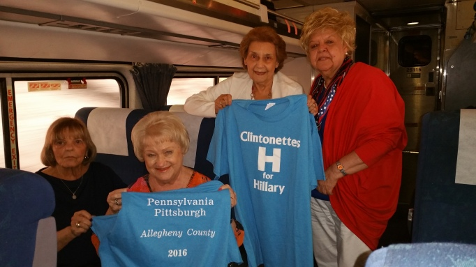 "Picture of Ruth Pastore, Jean Mllko, Angie Gialloreto, and Norma McCuen holding up two t-shirts that say ""Clintonettes H for Hillary"" on the front and ""Pennsylvania Pittsburgh Allegheny County 2016"" on the back."