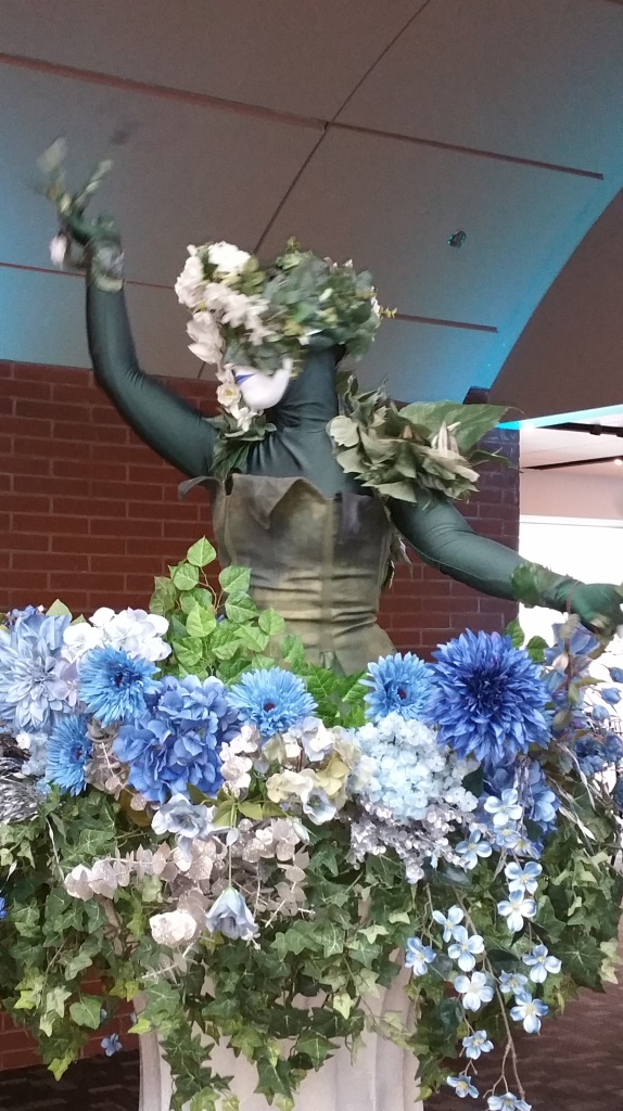 picture of One of the live-action flower women at the Kimmel Center standing in a large flower urn waving her arms.