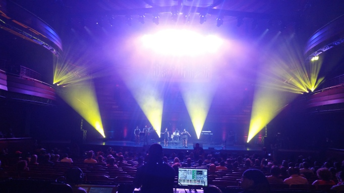 Picture of the stage at Verizon Symphony Hall at the Kimmel Center with yellow spotlights on the variety show stage.