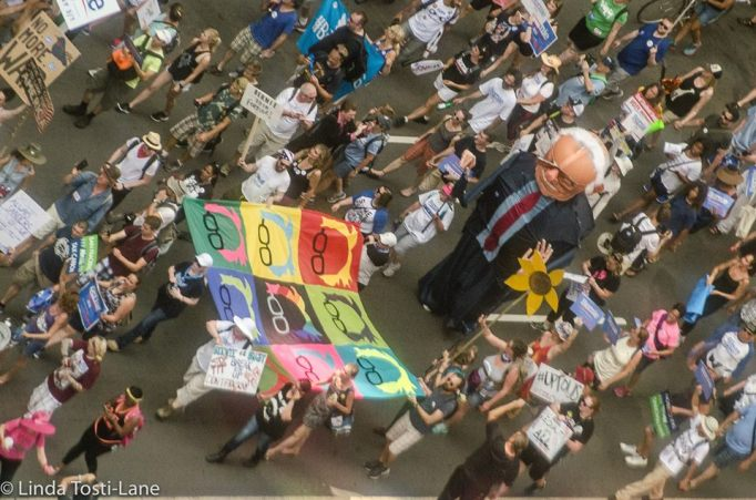 Picture of a larger than life-size Bernie sanders blow-up puppet marching down Broad Street with 100's of his supporters.