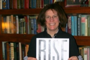 "Joanne standing in front of a bookcase holding up a sign saying ""Rise"" to action"