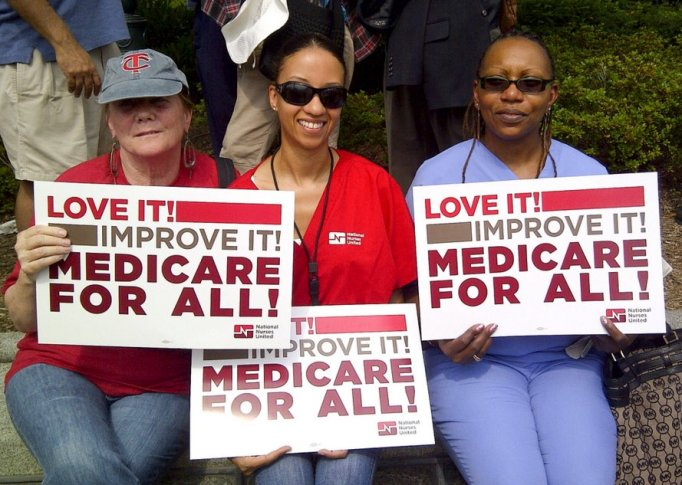 "Three women holding up posters that say ""Love it! Improve it! Medicare for All!"""