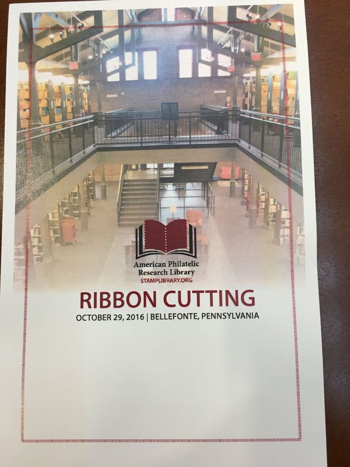 "Picture of the APRL Library from the 2nd floor with the organizational logo and the words ""American Philatelic Research Library,"" ""Stamplibrary.org,"" ""Ribbon Cutting,"" and date and town printed on top of the picture"
