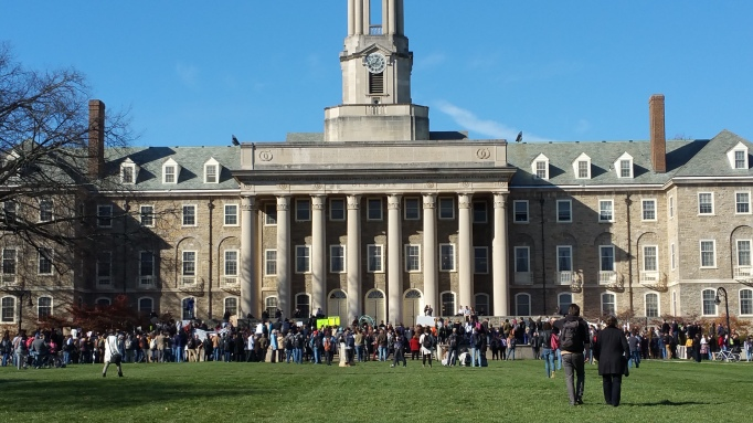 "picture of PSU's Old Main Building surrounded by students, faculty, staff, and community members at the ""#NotMyPresident Walk-Out/Love Trumps Hate"" Rally"
