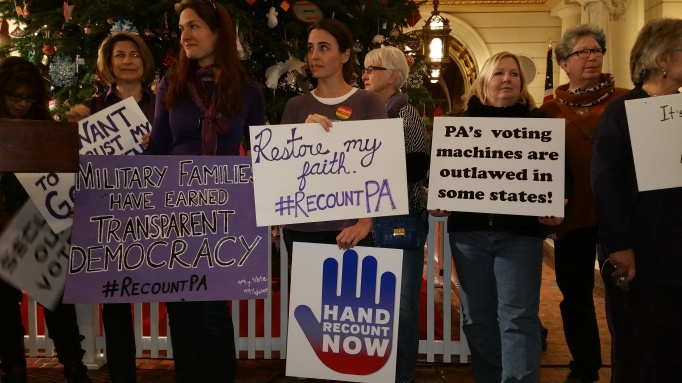 Picture of people holding signs about why they want a recount of the Presidential and US Senate races in the 2016 elections in Pennsylvania