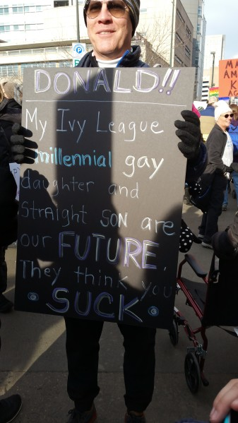 "Picture of a father carrying a sign that says, ""Donald!! My Ivy League millennial gay daughter and straight son are our FUTURE. The thin you ""SUCK."""