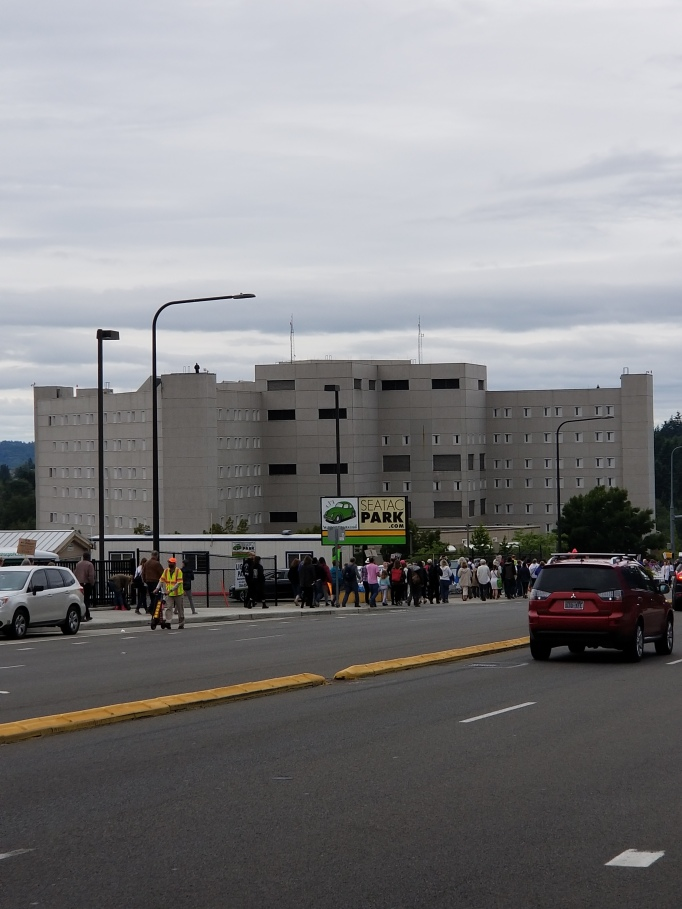 picture of the Federal Detention Center with cars driving down street and people walking towards the rally in front of the building
