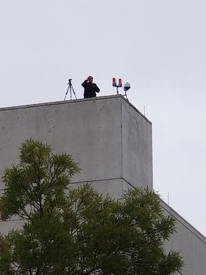 picture of a federal agent surveilling the crowd attendees.