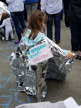 "picture of a child wearing aluminum foil with a sign saying that the statement ""Fake News! No Immigration Crisis!"""