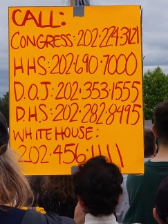 Sign listing the DC phone numbers for Congress (202-224-3121), Health and Human Services (202-690-7000), Department of Justice (202-353-1555), Department of Homeland Security (202-282-8995), and the White House (202-456-1111)