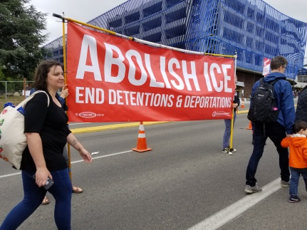 "Banner reading, ""Abolish ICE. End Detentions & Deportations"""