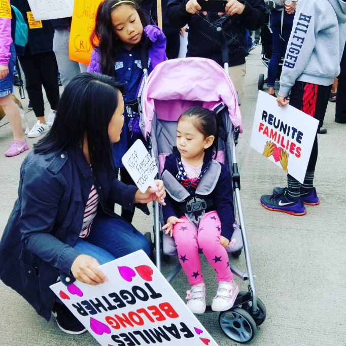 "Picture of a girl sitting in a stroller with her mother and sister holding signs that say, ""Families belong together."""